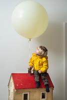 Boy sitting on dolls house looking up at balloon 11015318142| 写真素材・ストックフォト・画像・イラスト素材|アマナイメージズ