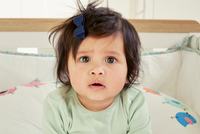 Close up portrait of baby girl staring from crib 11015318201| 写真素材・ストックフォト・画像・イラスト素材|アマナイメージズ
