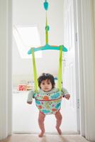 Portrait of baby girl staring from baby bouncer 11015318205| 写真素材・ストックフォト・画像・イラスト素材|アマナイメージズ