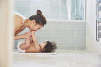 Woman playing with baby daughter's feet on bathroom floor 11015318214| 写真素材・ストックフォト・画像・イラスト素材|アマナイメージズ