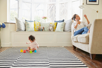 Woman with baby daughter reclining on sofa making smartphone call 11015318219| 写真素材・ストックフォト・画像・イラスト素材|アマナイメージズ