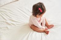 Overhead view of baby girl sitting up on bed 11015318231| 写真素材・ストックフォト・画像・イラスト素材|アマナイメージズ