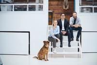 Portrait of male and female design team sitting on design studio stairs 11015318540| 写真素材・ストックフォト・画像・イラスト素材|アマナイメージズ