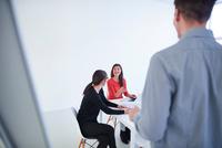 Colleagues in office watching presentation 11015318553| 写真素材・ストックフォト・画像・イラスト素材|アマナイメージズ