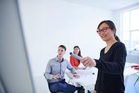 Colleagues in office watching presentation 11015318554| 写真素材・ストックフォト・画像・イラスト素材|アマナイメージズ