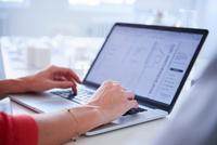 Cropped view of woman using laptop 11015318557| 写真素材・ストックフォト・画像・イラスト素材|アマナイメージズ