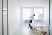 Architect in office with blueprint looking at architectural model 11015318568| 写真素材・ストックフォト・画像・イラスト素材|アマナイメージズ