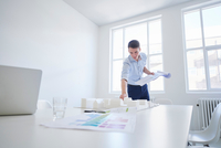 Architect in office with blueprint looking at architectural model 11015318569| 写真素材・ストックフォト・画像・イラスト素材|アマナイメージズ