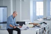 Man in open plan office looking at blueprint 11015318616| 写真素材・ストックフォト・画像・イラスト素材|アマナイメージズ