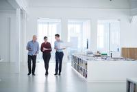 Colleagues walking through open plan office 11015318619| 写真素材・ストックフォト・画像・イラスト素材|アマナイメージズ