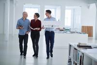 Colleagues walking through open plan office 11015318622| 写真素材・ストックフォト・画像・イラスト素材|アマナイメージズ
