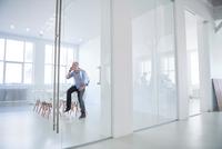 Man sitting on desk in office making telephone call on mobile phone 11015318630| 写真素材・ストックフォト・画像・イラスト素材|アマナイメージズ