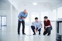 Colleagues working in open plan office looking at blueprints 11015318635| 写真素材・ストックフォト・画像・イラスト素材|アマナイメージズ