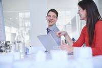 Colleagues using laptop, chatting and smiling 11015318641| 写真素材・ストックフォト・画像・イラスト素材|アマナイメージズ