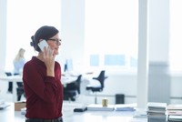 Woman in office making telephone call using mobile phone 11015318655| 写真素材・ストックフォト・画像・イラスト素材|アマナイメージズ