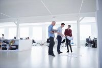 Colleagues working in open plan office looking at blueprints 11015318656| 写真素材・ストックフォト・画像・イラスト素材|アマナイメージズ