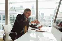 Businessman reading and analysing report, London, UK 11015318857| 写真素材・ストックフォト・画像・イラスト素材|アマナイメージズ