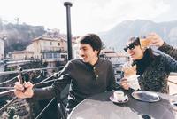 Couple taking smartphone selfie at restaurant, Monte San Primo, Italy 11015319305| 写真素材・ストックフォト・画像・イラスト素材|アマナイメージズ