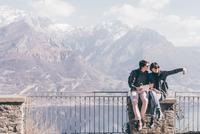 Couple sitting on terrace wall over mountain lakeside, Monte San Primo, Italy 11015319314| 写真素材・ストックフォト・画像・イラスト素材|アマナイメージズ