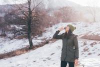 Female hiker drinking water in snow, Monte San Primo, Italy 11015319351| 写真素材・ストックフォト・画像・イラスト素材|アマナイメージズ