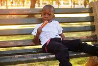 Boy eating ice lolly on bench 11015319603| 写真素材・ストックフォト・画像・イラスト素材|アマナイメージズ