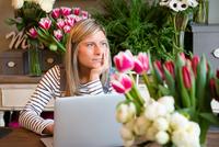 Florist worker in flower shop, using laptop, bored expression 11015319623| 写真素材・ストックフォト・画像・イラスト素材|アマナイメージズ
