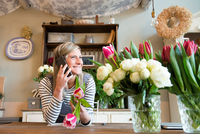 Florist in flower shop, using smartphone 11015319624| 写真素材・ストックフォト・画像・イラスト素材|アマナイメージズ