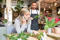 Female florist talking on smartphone, male colleague preparing flower order behind her 11015319631| 写真素材・ストックフォト・画像・イラスト素材|アマナイメージズ