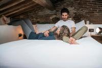 Romantic young couple reclining on bed 11015319680| 写真素材・ストックフォト・画像・イラスト素材|アマナイメージズ