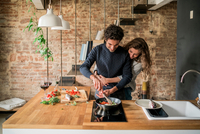 Young couple cooking fish cuisine at kitchen counter hob 11015319692| 写真素材・ストックフォト・画像・イラスト素材|アマナイメージズ