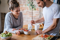 Young couple eating fruit breakfast at kitchen counter 11015319704| 写真素材・ストックフォト・画像・イラスト素材|アマナイメージズ