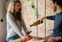 Young couple pouring red wine at kitchen counter 11015319705| 写真素材・ストックフォト・画像・イラスト素材|アマナイメージズ