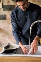 Young man washing fish at kitchen sink 11015319706| 写真素材・ストックフォト・画像・イラスト素材|アマナイメージズ