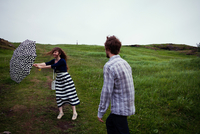 Couple standing in field on windy day, young woman's umbrella caught in wind 11015319783  写真素材・ストックフォト・画像・イラスト素材 アマナイメージズ