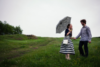 Couple standing in field, holding hands, young woman holding umbrella 11015319785| 写真素材・ストックフォト・画像・イラスト素材|アマナイメージズ