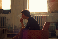 Young man sitting on vintage armchair in artist studio smoking cigarette 11015319800| 写真素材・ストックフォト・画像・イラスト素材|アマナイメージズ