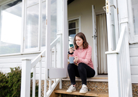 Young woman sitting on porch stairs with coffee cup looking at smartphone 11015319815  写真素材・ストックフォト・画像・イラスト素材 アマナイメージズ