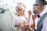 1950's vintage style mature woman wiping boyfriend's beard on pier 11015320101| 写真素材・ストックフォト・画像・イラスト素材|アマナイメージズ