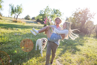 Young man having fun carrying girlfriend in field, Majorca, Spain 11015320193| 写真素材・ストックフォト・画像・イラスト素材|アマナイメージズ