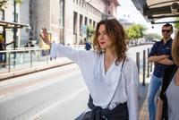 Young woman hailing a bus at city bus stop, Beyazit, Turkey 11015320297| 写真素材・ストックフォト・画像・イラスト素材|アマナイメージズ