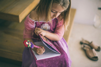 Young girl wearing princess dress, sitting on stairs, writing in book 11015320621| 写真素材・ストックフォト・画像・イラスト素材|アマナイメージズ