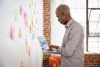 Young man standing in front of white board with sticky notes, using laptop 11015320711| 写真素材・ストックフォト・画像・イラスト素材|アマナイメージズ