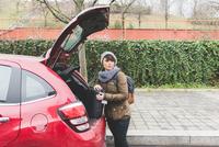 Female backpacker removing sleeping bag from car boot in city 11015320901| 写真素材・ストックフォト・画像・イラスト素材|アマナイメージズ