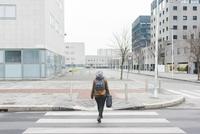 Rear view of female backpacker walking over city pedestrian crossing 11015320902| 写真素材・ストックフォト・画像・イラスト素材|アマナイメージズ