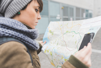 Female backpacker with smartphone looking at map in city 11015320903| 写真素材・ストックフォト・画像・イラスト素材|アマナイメージズ