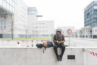 Female backpacker sitting on wall selecting smartphone music 11015320906| 写真素材・ストックフォト・画像・イラスト素材|アマナイメージズ