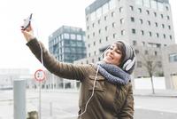 Mid adult woman taking smartphone selfie in city 11015320907| 写真素材・ストックフォト・画像・イラスト素材|アマナイメージズ