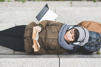 Overhead view of female backpacker lying on back reading book on wall 11015320910| 写真素材・ストックフォト・画像・イラスト素材|アマナイメージズ