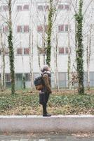 Female backpacker standing on office buildings wall 11015320913| 写真素材・ストックフォト・画像・イラスト素材|アマナイメージズ