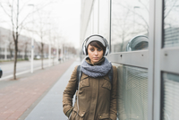 Portrait of mid adult woman listening to headphones and leaning against city office block 11015320915| 写真素材・ストックフォト・画像・イラスト素材|アマナイメージズ